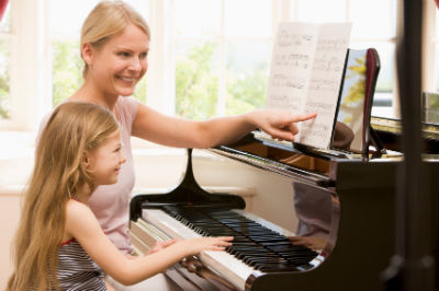 Young woman teaches a little girl to play the piano